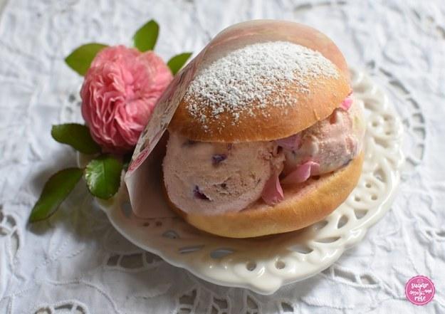 Eisburger (Brioche con Gelato) in einer Papiertüte mit Rosendekor, liegend auf einem Keramikteller auf einem einem weißen Platzset mit Lochmuster, dekoriert mit einer rosa Rosenblüte der Rose Leonardo de Vinci