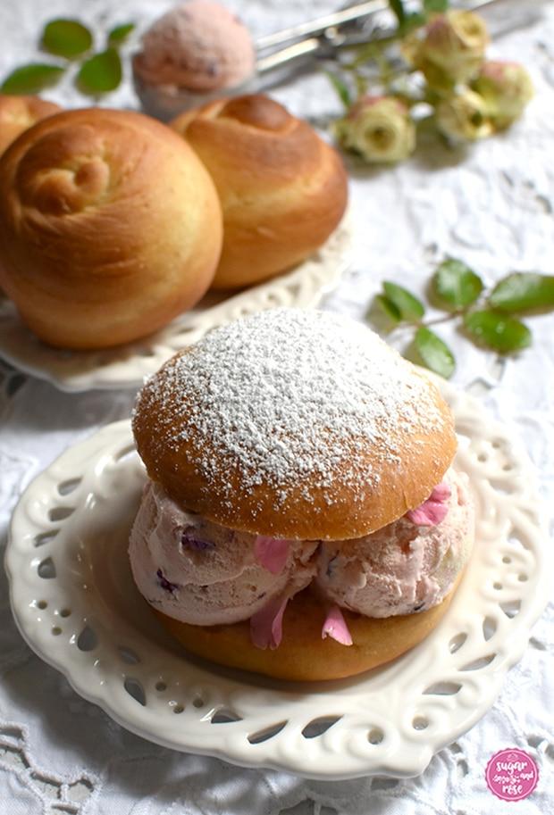 Eisburger (Brioche con Gelato) in gefüllt mit Roseneiskugeln auf Vintageteller, dahinter ein ebensolcher Keramikteller mit ungefüllten Brioschknöpfen, ein Eisportionierer mit einer Kugel Eis und daneben kleine grüne Rosen