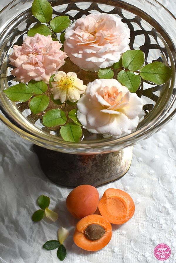 Art-Deco-Schale mit Fuß in altem Silber mit einem passenden Glaseinsatz. In der Schale schwimmend im Wasser drei Blüten der apricotfarbenen Rose Schloss Eutin, einige hellgrüne Rosenblätter und eine winzig kleine pastellgelbe Rosenblüte, davor einige Marillen, eine davon aufgeschnitten mit sichtbarem Kern