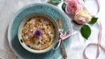 Porridge mit bunten Wiesenblumen in einer Steingut-Bowl auf türkisem Teller, daneben ein alte Silberlöffel mit rosa Masche und rosa Rosen mit Band im Hintergrund