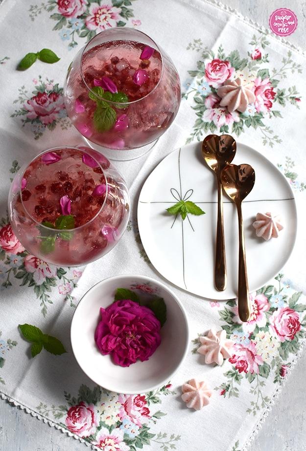 Rosé-Gin-Cocktail mit Granatapfelkernen in zwei Cognac-Schwenkern, daneben ein zarter weißer Porzellanteller mit zwei rosegoldfarbenen, herzförmigen Metalllöffelchen, eine Schale mit einer pinkfarbenen Rose und zartrosa Baisertuffs auf einer weißen Leinenserviette mit zartrosa Rosenmotiven