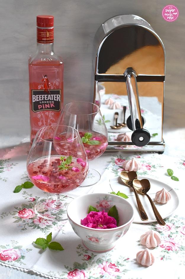Rosé-Gin-Cocktail mit Granatapfelkernen in zwei Cognac-Schwenkern, daneben ein Porzellanteller mit zwei rosegoldfarbenen, herzförmigen Metalllöffelchen, eine Schale mit einer pinkfarbenen Rose und Rosenmotiv im Vordergrund. Alles steht auf einer weißen Leinenserviette mit zartrosa Rosenmotiven. Links hinten steht eine Flasche Beefeater London Pink Gin, daneben ein Eiscrusher mit Hebel für Handantrieb.