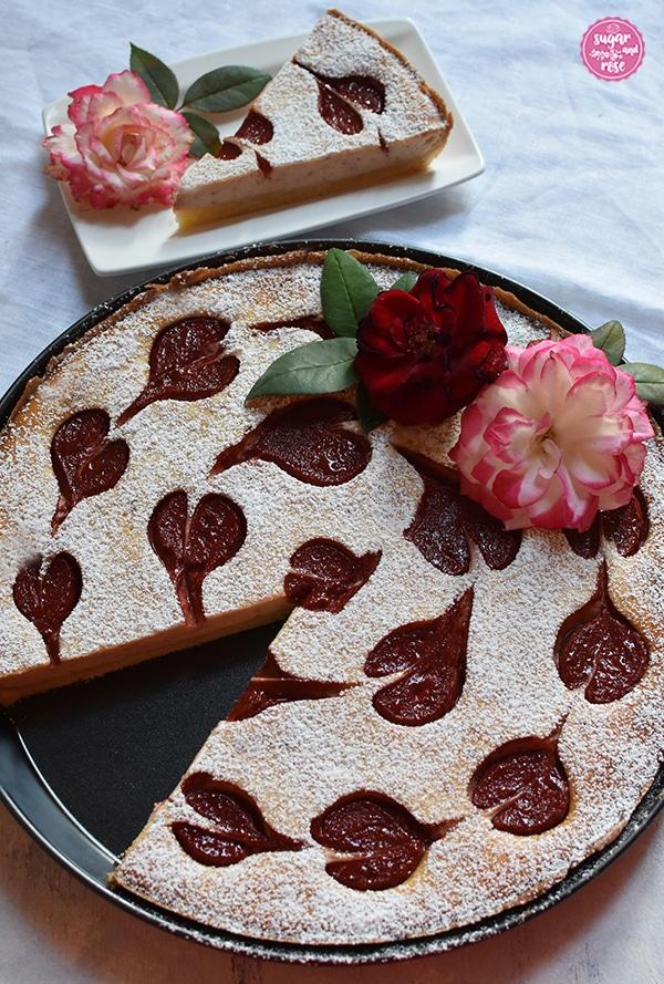 Herzerl-Ricotta-Tarte mit Zwetschkenmus in einer runden Tarteform. Ein Stück fehlt. Es steht im Hintergrund auf einem weißen Keramikteller und man sieht den Anschnitt des Kuchens.