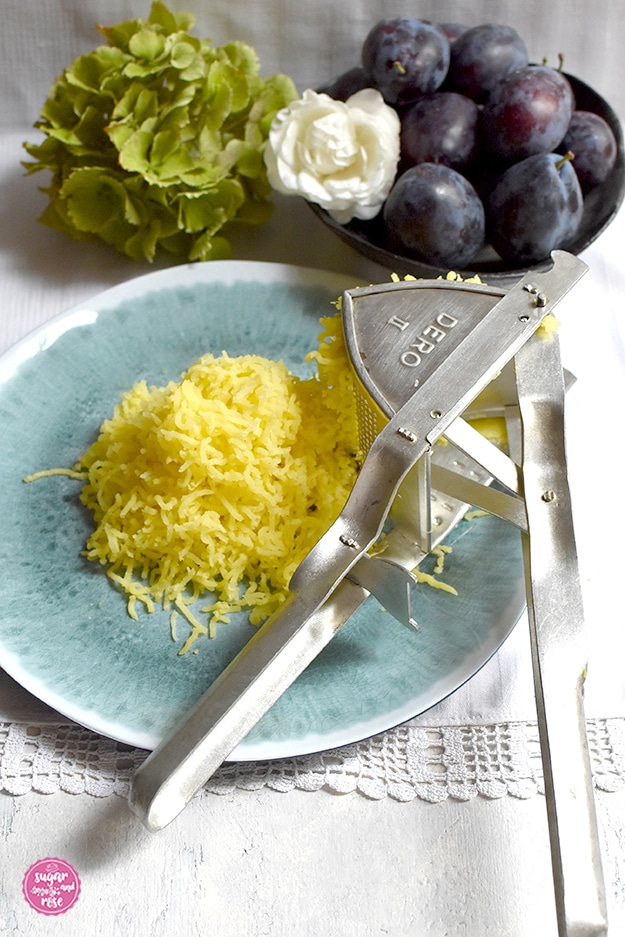 Ein mintgrüner Melaminteller mit frisch gepressten Kartoffeln und einer Kartoffelpresse, dahinter eine dunkelgraue Tonschale mit Zwetschken und weißer Rosenblüte