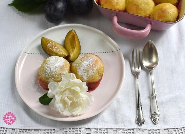 Großaufnahme des rosa-weißen Dessertellers mit zwei gebackenen Zwetschkenknödeln, zwei Zwetschkenspalten, daneben Gabel und Löffel, im Hintergrund der Griff der rosa Pfanne sichtbar. Alles steht auf einem alten weißen Leinentuch mit gehäckelter weißer Spitzenborte.