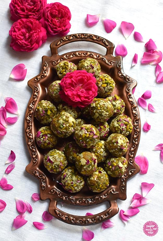 Kupfertablett mit Henkeln, darauf ein Menge Rosen-Safran-Energiekugeln, obenauf eine Rosenblüte, rund um das Tablett einzelne Rosenpetalen der Rose de Resht