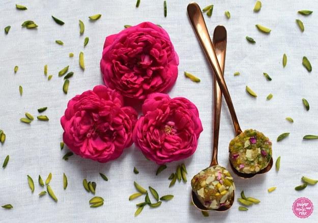 Weißes Leinentischtuch mit grünen Pistazienstiften bestreut, in der Mitte drei pinkfarbene Rosen, daneben zwei kupferfarbene Herzlöffelchen mit überkreuzten Stielen. Auf den Löffeln je ein halbierter Energyball