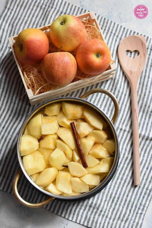 Auf einer grau-weiß gestreiften alten Leinenserviette ein Topf gefüllt mit Apfelspalten und Wasser, einer Zimstange und Gewürznelken. Daneben ein Holzkochlöffel, bei dem vorne ein Herz ausgestanzt ist. Dahinter eine Miniobstkiste mit Holzwolle, darin vier Äpfel