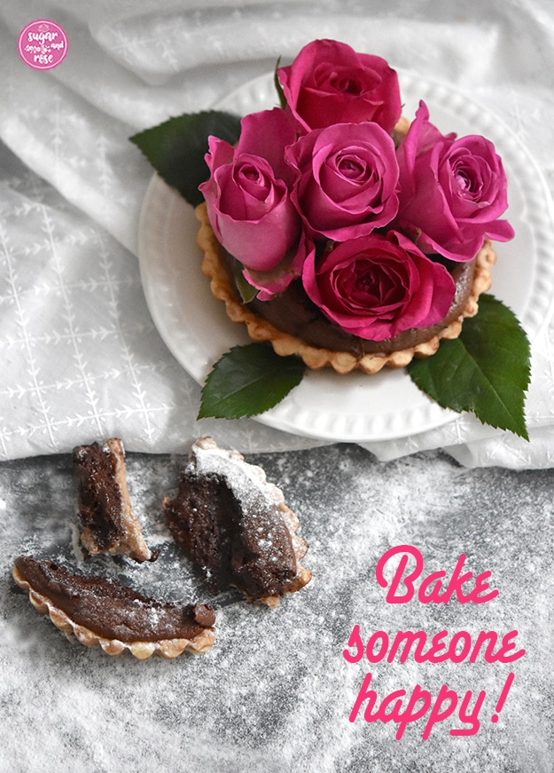 """Ein Schokotartelette auf weißem Vintageteller mit fünf pinkfarbenen Rosen in Großaufnahme auf weißem Stofftuch, dieses auf mit Puderzucker dicht bestreuter Arbeitsplatte und ein angebrochenes Stück eines Tartelettes. Auf dem Bild steht rechts unten in pinkfarbener Schrift """"Bake someone happy!"""""""
