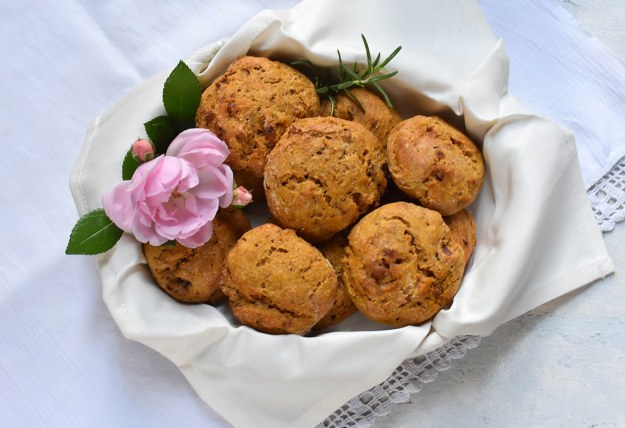 Brotkörbchen mit Stoffserviette gefüllt mit kleinen Kürbis-Speckweckerln und einer rosa Rosenblüte
