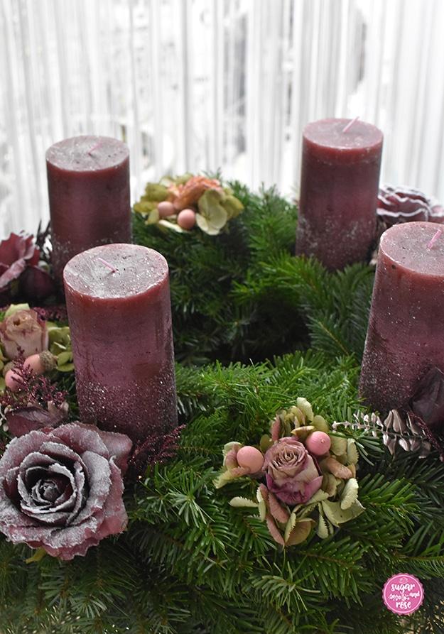 Adventskranz mit dicken weinroten Kerzen, dekoriert mit weinroten Kunstrosen mit Schneespray, dazwischen Hortensienblüten und getrocknete rosa Rosen