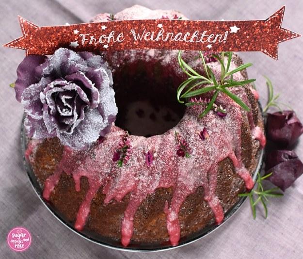 """Punschgugelhupf von oben, dekoriert mit einer auberginefarbenen Seidenblüte mit Schneestaub, Rosmarinzweigen und getrockneten dunkelrosa Rosenblüten, on the top ein weinrotes Schildchen mit der Aufschrift """"Frohe Weihnachten"""""""