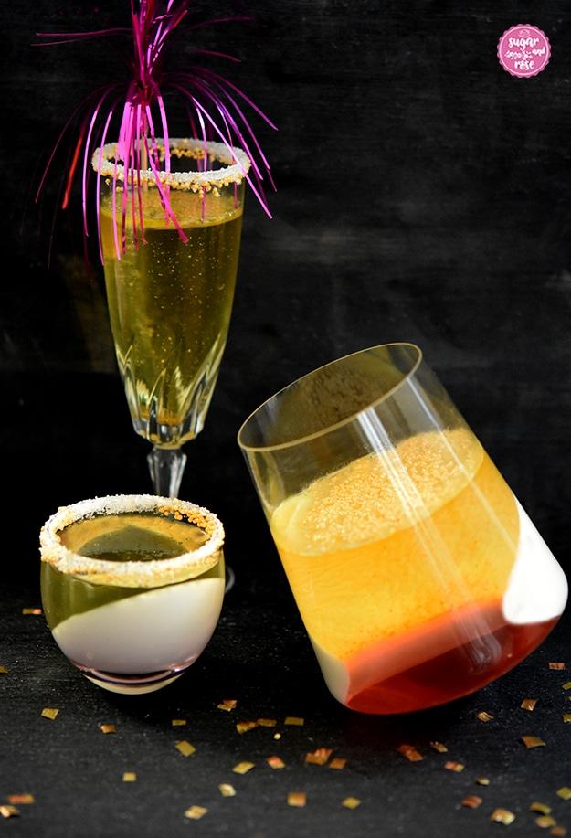 Ein Sektglas mit Sektjelly und pinkfarbener Cocktaildrink-Deko, davor ein bauchiges Glas mit Sektjelly und Wodka-Pannacotta, daneben ein Glas mit dreifarbigem Sektjelly (gold, weiß, rot)