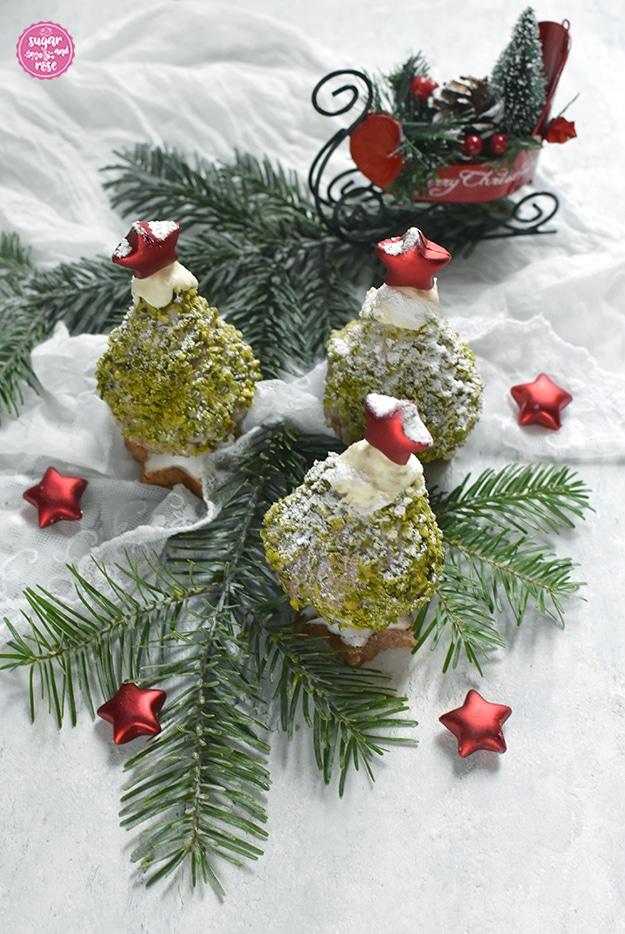 Drei Weihnachstbäume zum Vernaschen auf angezuckerten Tannenzweigen, dahinter ein roter Dekoweihnachtsschlitten, vorne kleine rote Dekosterne