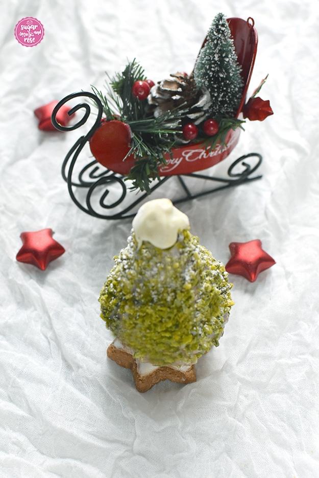 """Ein süßer Weihnachtsbaum zum Vernaschen mit Pistazienkleid, auf einem Zimtstern stehend, an der Spitze weiße Kuvertüre, drei rote Dekosterne und der rote Dekometallschlitten mit der Aufschrift """"Merry Christmas"""""""