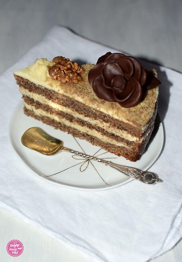 Ein Stück Walnusstorte auf einem kleinen weißen Porzellanteller mit goldener Masche als Dekor, dazu ein alter englischer Silberlöffel. Das Tortenstück mit karamellisierter Walnusshälfte und einer Schokoladenrosenblüte wird auf einer weißen Leinenserviette präsentiert.