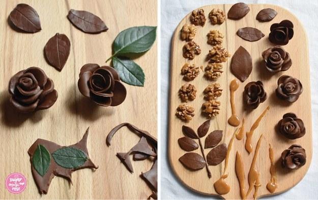 Links zwei fertige Schokoladerosen, Reste der Modellierschokolade und grüne Rosenblätter; rechts auf einem Holzbrett fertige Rosenblüten und Blätter aus Modellierschokolade sowie karamellisierte Walnusshälften