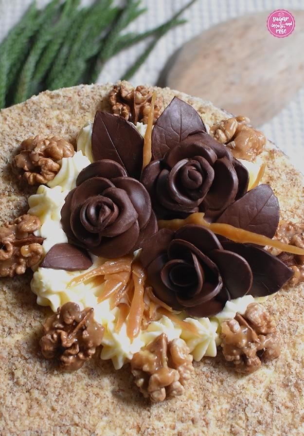 Detailausschnitt der Dekoration auf der Walnusstorte: ein weißes Cremebett auf einem Teil der Oberfläche, darauf drei Schokoladenblüten mit Blättern, dazwischen Krokantstangen, rund um die Creme die karamellisierten Walnusshälften