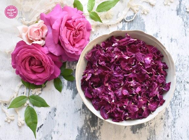 Eine Schale mit getrockneten dunkelrosa Blüten der Rose de Resht, dahinter drei frische rosa Rosenblüten, grüne Rosenblätter und ein zartes cremefarbenes Vintagetuch