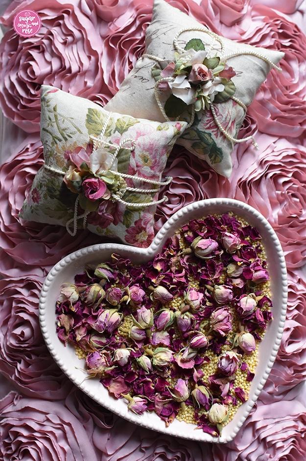 Rosa Herzschale mit Hirsespelzen und Rosenknospen, dahinter auf einem Kissen mit Seidenrosen als Oberfläche zwei quadratische Rosenduftkissen mit Kordeln und Seidenblütendekoration