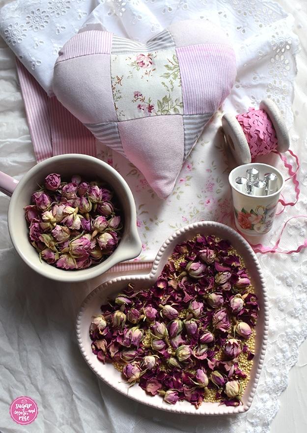 Rosenduftkissen in Herzform aus rosa-weiß gestreiftem, rosafarbenen und geblümten Stoffresten im Patchworkstil, davor eine Schale mit getrockneten Rosenblüten, Rosenöl-Phiolen, ein rosa Stoffband auf Spule und eine Herzschale mit Rosenblütenknospen