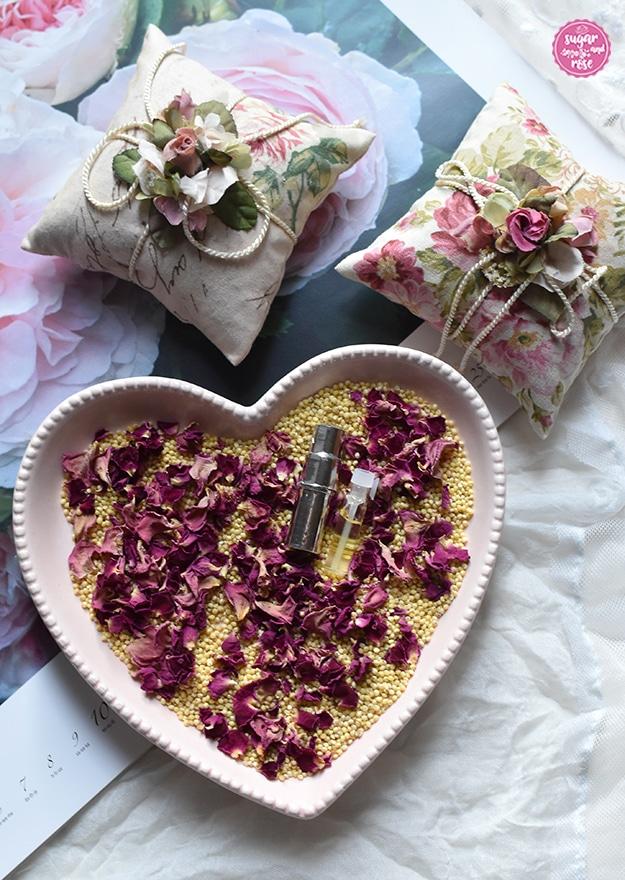 Zwei quadratische Rosenkissen aus Rosendekorstoff, umwickelt mit weißer Kordel, dekoriert mit Seidenblüten, davor eine rosa herzförmige Schale mit Hirsespelzen, getrockneten Rosenblüten und Rosenöl-Phiolen