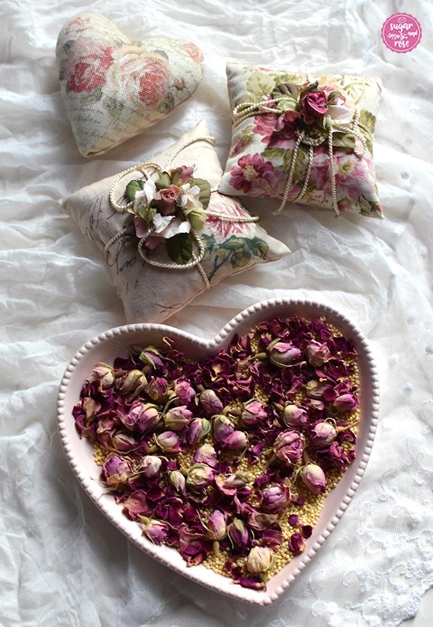 Im Vordergrund eine dezent rosa Herzschale mit Hirsespelzen und Rosenknospen, dahinter auf einem weißen Spitzenschal zwei quadratische und ein herzförmiges Rosenduftkissen mit Rosendekorstoff