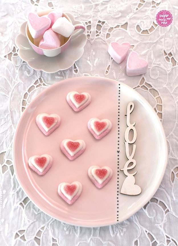 Rosa-weißer Keramikteller mit sieben dekorativ aufgelegten Zuckerherzen, dahinter eine Augarten-Melone-Mokkatasse mit rosa Marshmallowherzen gefüllt auf weißem Lochstickerei-Tischset