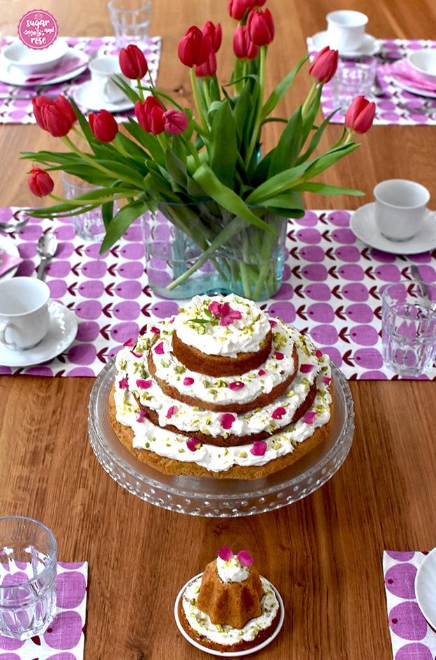 Frühstückstisch mit sechs Gedecken in weißem Porzellan, in der Mitte eine grüne Glasvase mit roten weinroten Tulpen, davor der Karottenkuchen mit Frischkäsefrosting auf der Glasetagere und davor ein kleines Küchlein