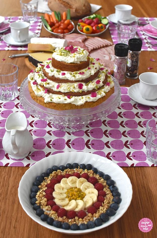 Frühstückstisch (Holz) mit rosa-weinroten nordischen Tischsets, in der Mitte die Glasetagere mit dem Karottenkuchen mit Frischkäsefrosting, davor eine weiße Schale mit Birchermüsli, dekoriert mit Heidelbeeren, Himbeeren und Banane. Im Hintergrund eine große runde Platte mit Schinken und Käse, Teller mit buntem Gemüse und ein großes Bauernbrot