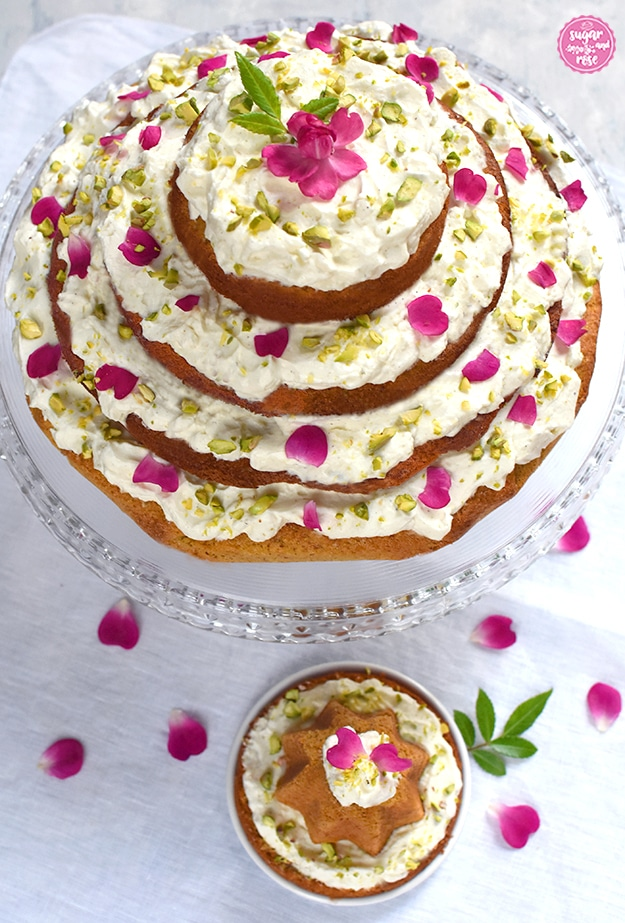Karottenkuchen mit Frischkäsefrosting auf Glasetagere von vorne, davor ein kleines Küchlein auf einem extra Teller, rundum pinke Rosenblüten verstreut