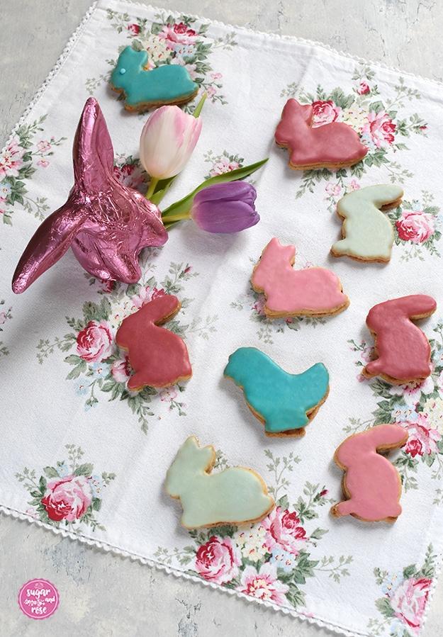 Osterhasen-Kekse in vier Pastellfarben glasiert auf Geschirrtuch mit Rosenmotiv, dazu ein Schokoosterhase in Pink und zwei Tulpenblüten