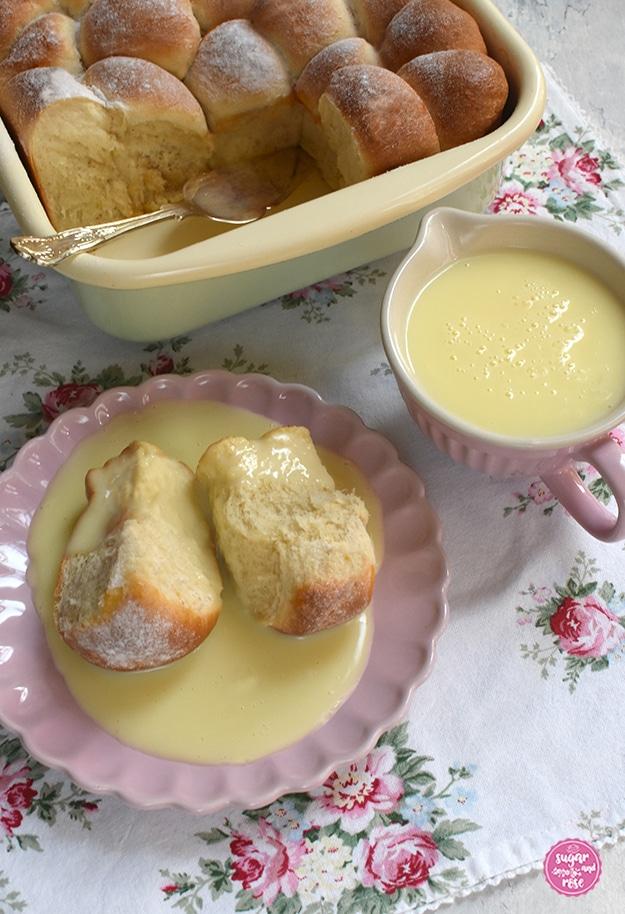 Marillenbuchteln in einer Riess-Pfanne auf Serviette mit Rosenmuster, einige Buchteln fehlen, dort liegt ein silberner Tortenheber. Davor ein rosa Keramikteller mit zwei Buchteln und Vanillesauce. Daneben eine rosa Keramikschale mit Henkel, gefüllt mit Vanillesoße