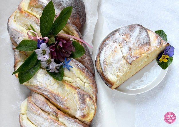 Topfen-Brioche dekoriert mit einem Frühlingsblumensträußchen, daneben ein Tellerchen mit einem Stück Topfenbrioche und einer Violenblüte
