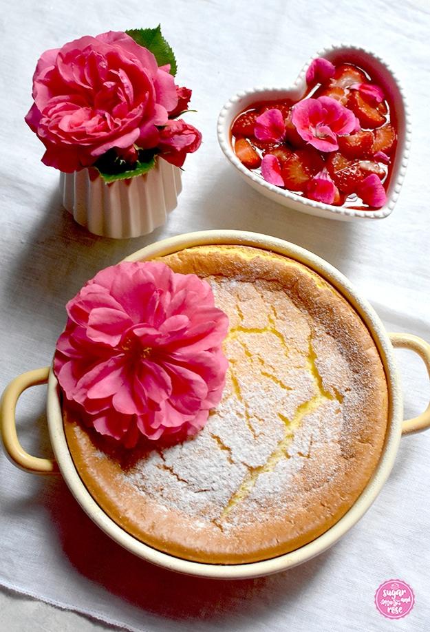 Grießauflauf in gelber Riess-Emailpfanne, dekoriert mit einer Rosenblüte, dahinter ein Erdbeer-Geranien-Kompott in herzförmiger Keramikschale, daneben eine kleine Vase mit einer pinkfarbenen Rosenblüte (Rosarium Uetersen)