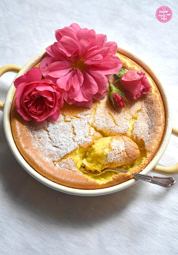 Grießauflauf in gelber Riess-Emailpfanne mit drei pinkfarbenen Rosenblüten dekoriert (Rosarium Uetersen); Auflauf mit einem silbernen Dessertlöffel an einer Stelle angestochen.