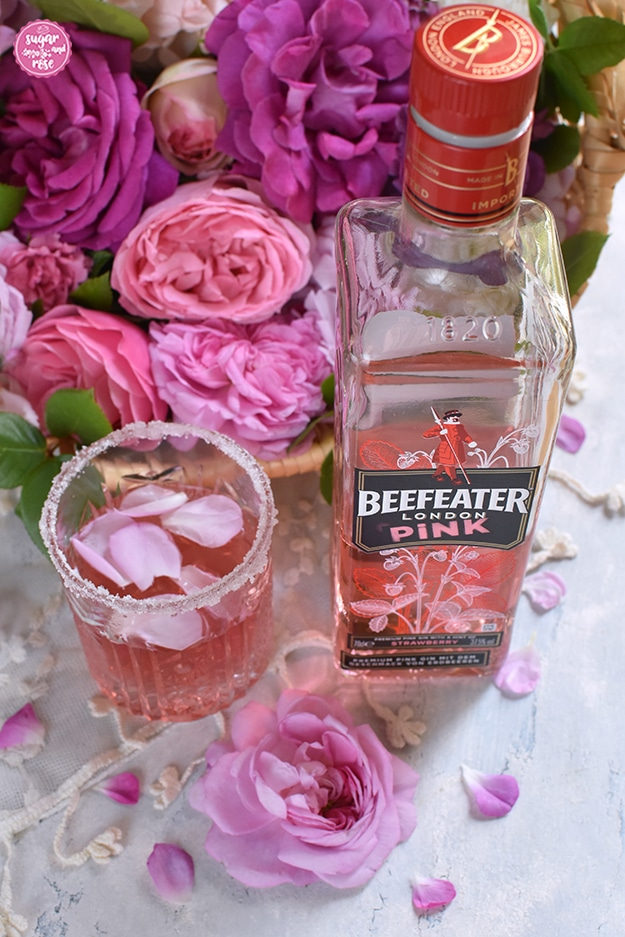 Pink Rosé Gin im Glas mit Zuckerrand, daneben eine Flasche Beefeater London Pink Gin, dahinter ein Korb mit rosa und piken Rosen