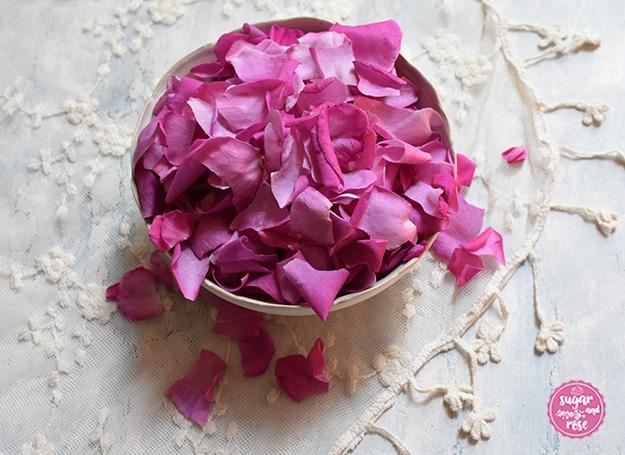 Eine weiße Keramikschale mit pinken Rosenblüten auf einem Vintagetuch mit aufgestickten Blüten
