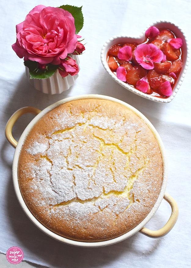Grießauflauf in gelber Riess-Emailpfanne mit Erdbeer-Geranien-Kompott in herzförmiger Keramikschale, daneben eine kleine Vase mit einer pinkfarbenen Rosenblüte (Rosarium Uetersen)