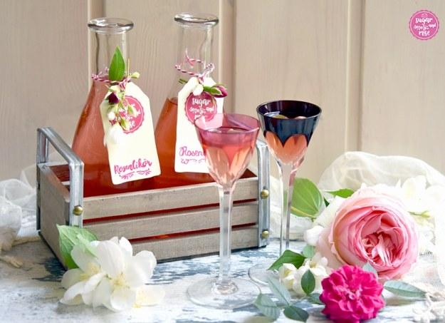 Rosenlikör in zwei Fläschchen abgefüllt und etikettiert in einer kleine hellen Holzkiste stehend, davor zwei Jugendstil-Likörgläser mit hohem Stil und Rosenblüten