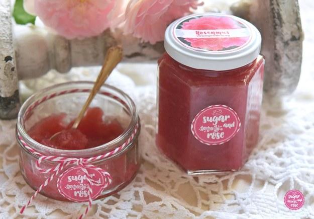Rosenmus in einem Marmeladeglas, beschriftet mit sugar&rose-Logo, daneben eine flache Glasschale mit Rosenmus und einem silbernen Löffelchen