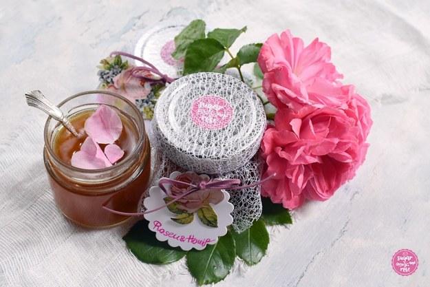 Zwei Gläser mit Rosenhonig, eines mit Deckel und weißem Netzstoff überzogen und mit Rosenetikette beschriftet und rosa Band, daneben ein geöffnetes Honigglas mit rosa Blüten und Silberlöffel; daneben rosa Blüten der Rosarium Uetersen