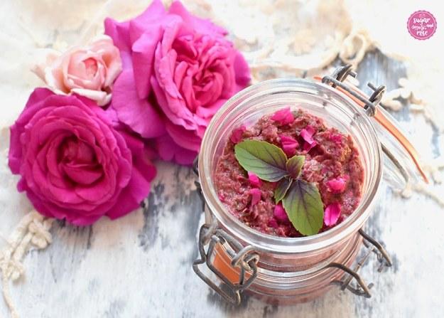 Rosenpesto in einem geöffneten  Weckglas, dekoriert mit rotem Basilikum, dahinter pinkfarbene Rosenköpfe
