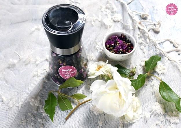 Rosenpfeffer in einem kleinen Schälchen und in einer Mühle mit schwarzem Deckel abgefüllt, davor weiße Rosen – für meine Rosenküche.