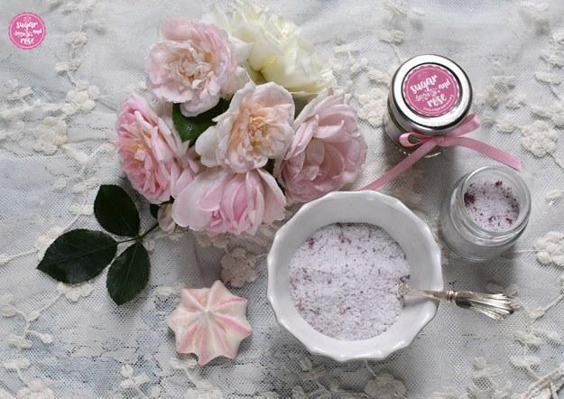 Rosenzucker in kleinen Gläsern abgefüllt, daneben pastellrosafarbene Rosenblüten, ein Baisertuff und eine weiße Schale mit Rosenblütenzucker und einem silbernen Löffelchen