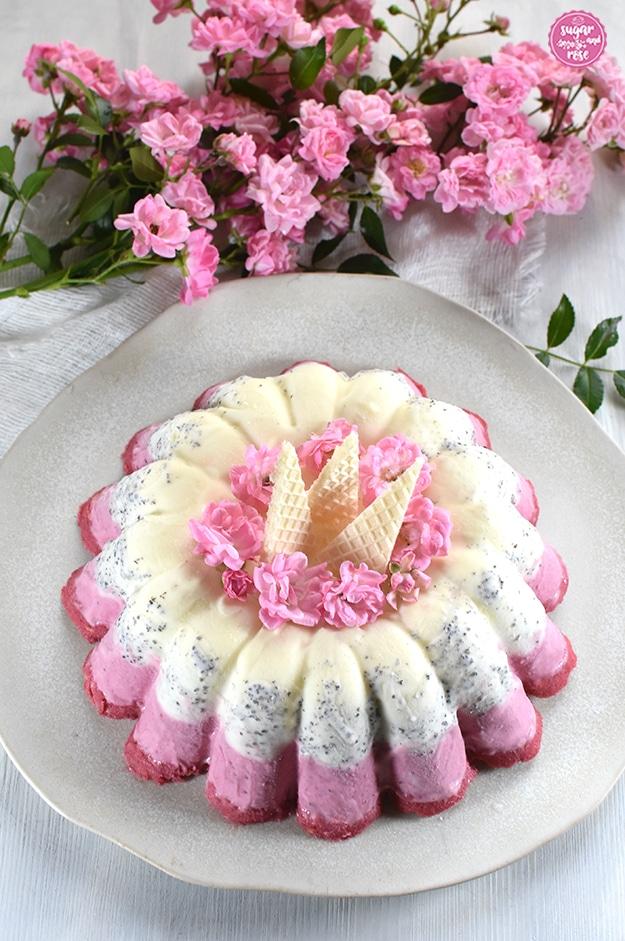 Eisgugelhupf auf unregelmäßig getöpfertem Teller, garniert mit kleinen rosa Röschen und dreieckigen Eiswaffeln, dahinter ein Zweig mit büschelweise rosa Röschen (The Fairy).