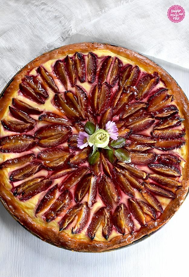 Frisch gebackene Zwetschkentarte, dekoriert mit einer kleinen hellgrünen Rosenblüte in der Kuchenmitte – auf weißem Untergrund mit weißem grobem Tuch
