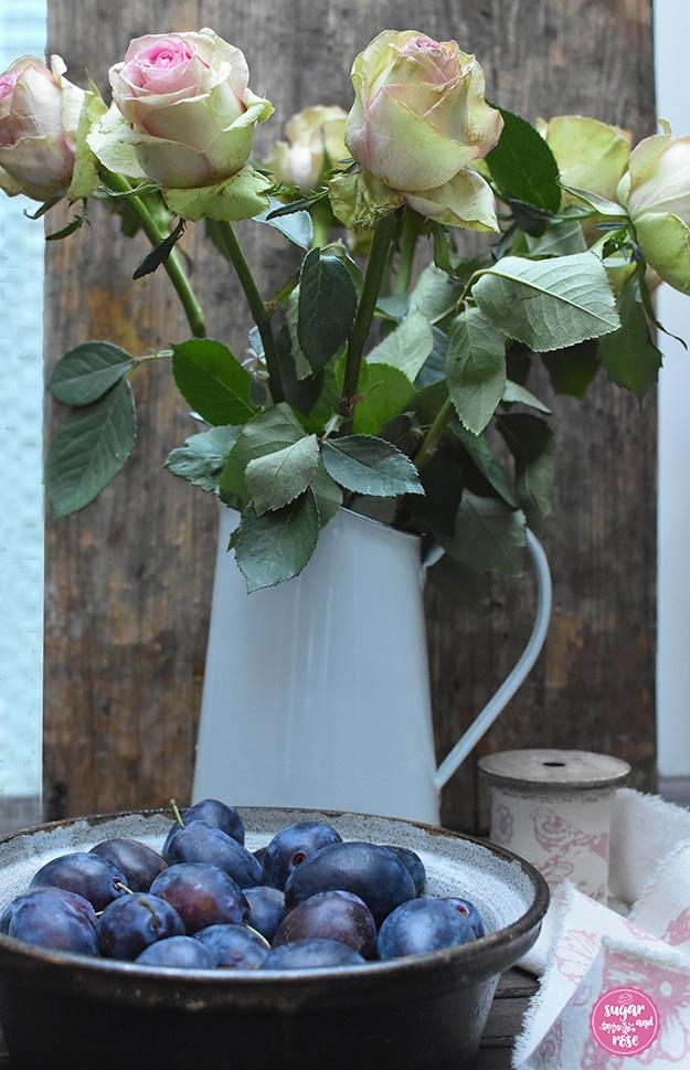Eine braune Keramikschale mit kräftig blauen Zwetschken gefüllt, dahinter ein weißer Metallkrug mit blassrosa-grünen Rosen, daneben eine Holzspule mit breitem Leinenband