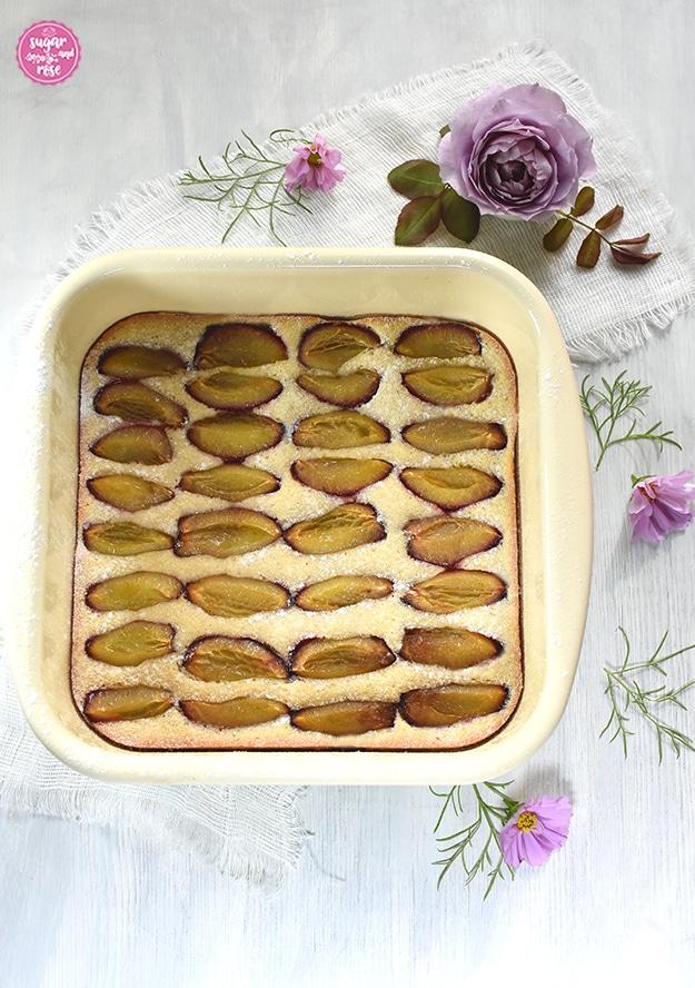 Obstkuchen mit Zwetschken in einer quadratischen Emailpfanne, dahinter eine lilafarbene Rosenblüte und einige rosa-lila farbene Cosmeablüten