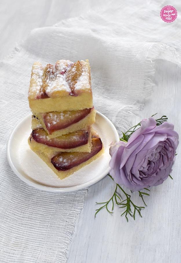 Drei Zwetschkenkuchenstücke übereinander gestapelt auf einem kleinen weißen Teller, darunter ein weißes grobes Stoffstück, dekoriert mit einer lila Novalis-Rosenblüte